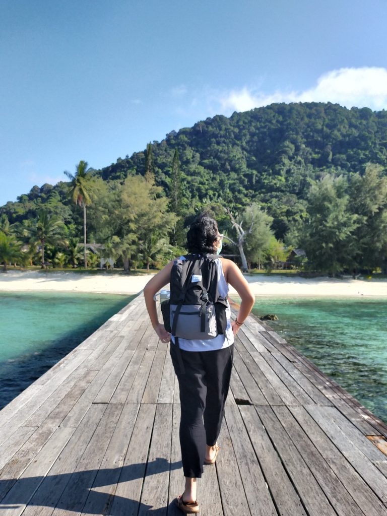 A view of the back of me (sleeveless white top, loose black pants, black and grey backpack, face mask slightly visible as my face is turned to the right) as I walk on a wooden jetty towards a sandy beach lined with palm trees, a dark green hump of a mountain in the background with the blue sky behind it, a wisp of white clouds just smearing the right side. On either side of the weathered jetty is turquoise water darkened by rocks