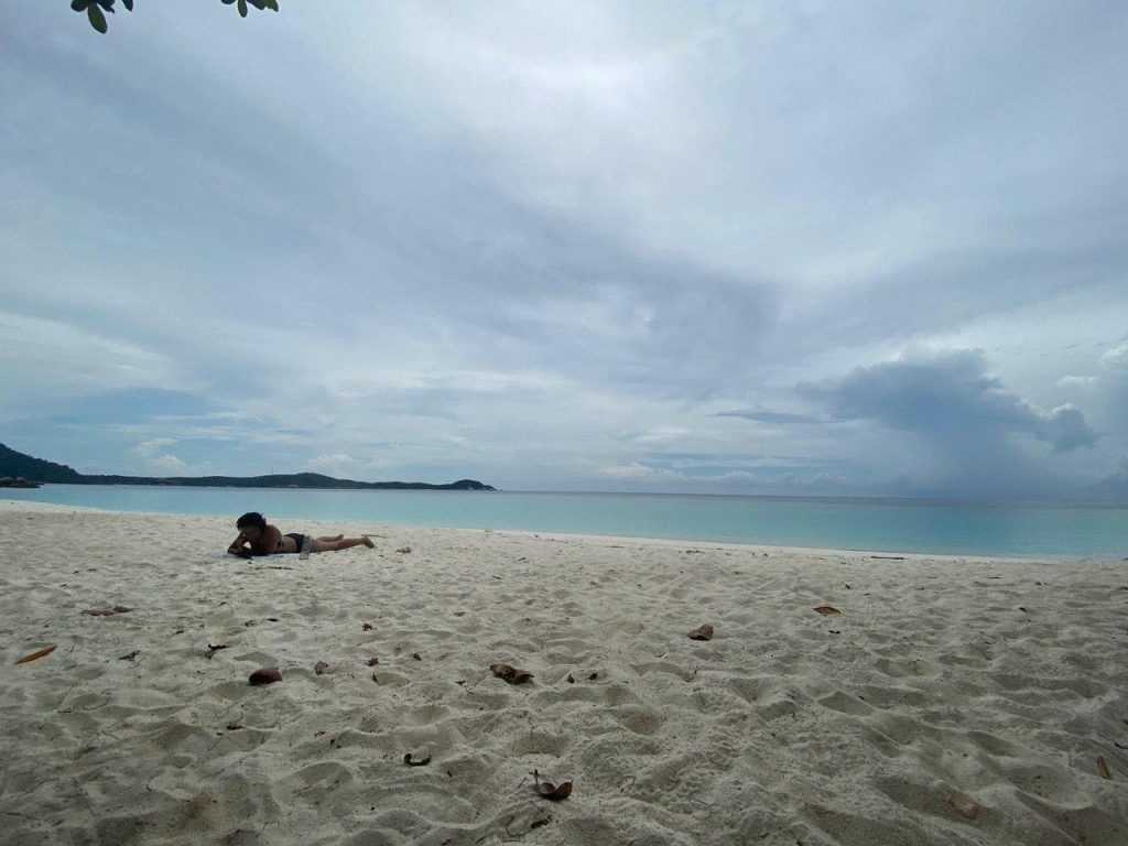 A beach photo with me in the lower third of the photo lying on my stomach on the sand, propped on my elbows to read a book. Behind me is the calm turquoise blue ocean, a small sliver of green of the opposing island on the horison to the left, and the light blue sky filled with flat white clouds filling up the rest of the background.